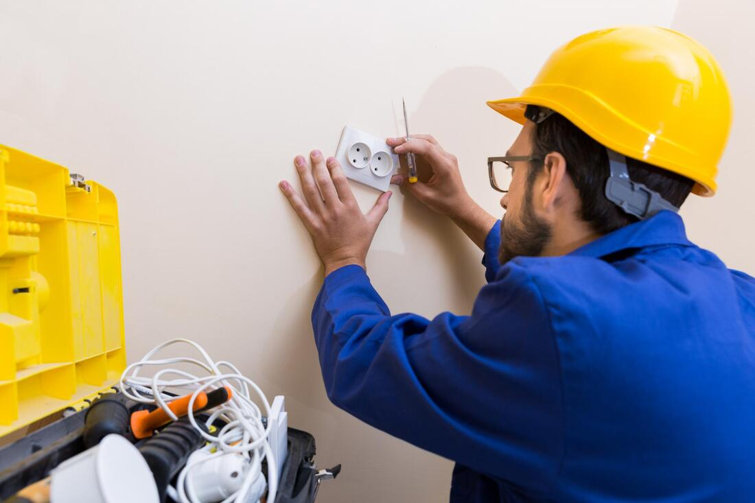man installing electrical socket